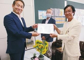 佐藤元治校長(左)に目録を手渡す古屋さん(右)。中央はドローン操縦士の中島芳男さん