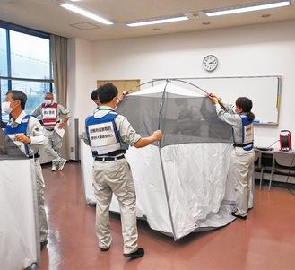 間仕切り用のテントを組み立てる職員たち