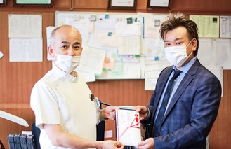 目録を手渡す和田剛支部長(右)