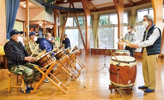 再現した楽譜をもとに太鼓や笛で音合わせをするメンバー