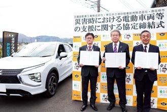 協定を締結した3者の代表と電動車両