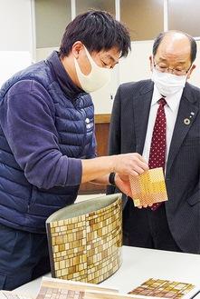 寄木細工の模様が入ったFRP花器を披露する東雄技研(株)の菊地代表(左)と説明を聞く秋葉理事長