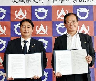 協定書を手にする湯川町長(右)と境町の橋本町長