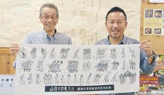 手拭いを広げる大野理事長(左)と池谷仁宏副理事長