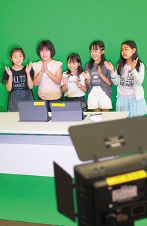 クロマキー合成の映像を撮影する児童