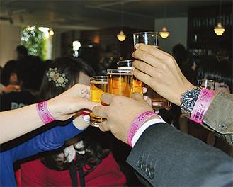 参加の証・ピンク色のリストバンドをつけた男女が乾杯
