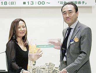 伊藤雅章副支配人から八神さんに、募金が手渡された