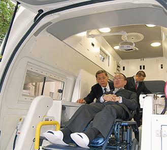 訪問車を体験する青木町長(中央)と河野会長(左)