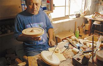 削り直した独楽を手にする伊藤さん 手のひらで回り具合を確かめる
