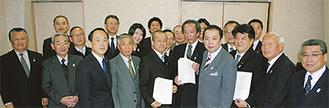 意見書案を手にした3会派の議員たち(19日・箱根町で)