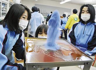 色粉を台の下から何度も噴出させ、火山を形作ってゆく