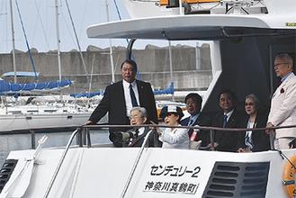 遊覧船に乗られるご夫妻と案内する室伏友三専務理事(右端)