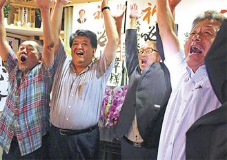 後援者や県議(左から2人目)たちと万歳する宇賀氏(右から2人目)