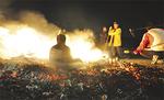 おき火に座る神像を囲んで団子を焼く=14日、強羅・東方之光敷地内