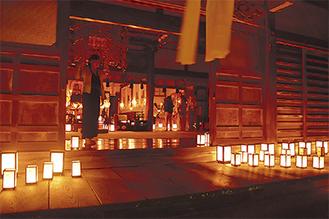 数十の灯篭に照らされた床を歩く参拝者
