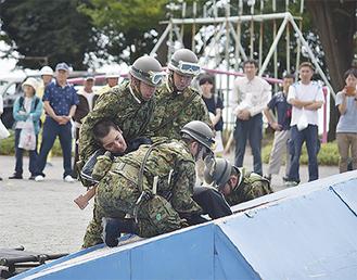 吉浜小校庭で陸自の救出訓練を見守る住民ら
