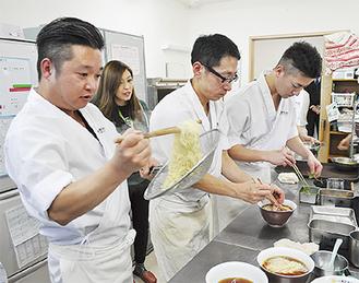 湯切りの音が響く厨房で盛り付ける飯田さん=左端