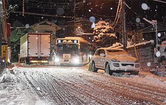 国道1号線・大平台バス停前で動けなくなったトラック(左)や車(右)を避けて通るバストラック運転手はタイヤ周りの雪をかきながら「この道は大丈夫かと思った」