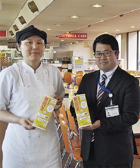 手作りの啓発ポップを持つ、食堂の松井美香店長(左)と環境政策課の大坪覚さん