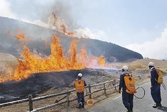 台ヶ岳側に立つ炎と水袋を背負って見守る関係者