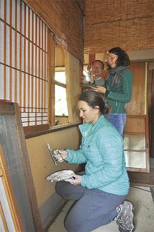 古民家の壁を塗る米国人の会社員とドイツ人学生