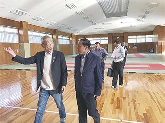 箱根仙石原キャンパスを案内する星槎の宮澤会長=左