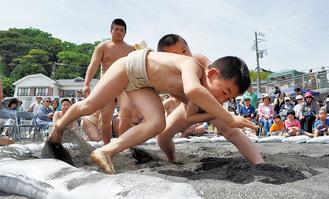 土俵際の攻防で砂を散らす