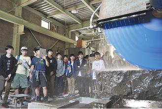 水を散らして回る切削機を撮影する生徒ら