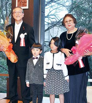 孫から贈られた花束を手に笑顔の小宮さん夫妻