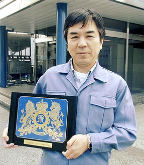 受賞の盾を手にする鈴木取締役工場長