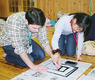 学生ボランティアが子どもたちから習字を教わる場面も