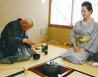真剣な表情でお茶を立てる植田さん(左)