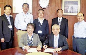 調印する栄一会長(前列右)と潔園長(前列左)