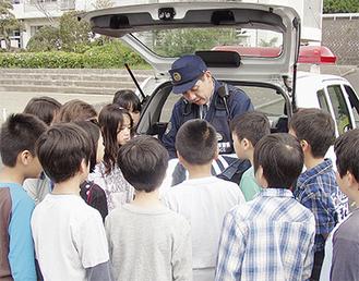 パトカーに積まれた荷物を見学する児童たち