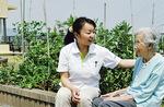 屋上庭園で団らんを楽しむ入居者とスタッフ。そら豆やいちごなどの家庭菜園も。