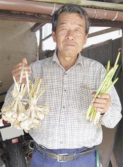 収穫したニンニク(左)とルバーブ(右)を笑顔で掲げる和田さん