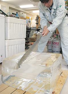 ブロック氷をのこぎりで切り分ける