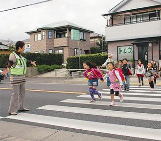 下校時間、横断歩道で小学生を見守る