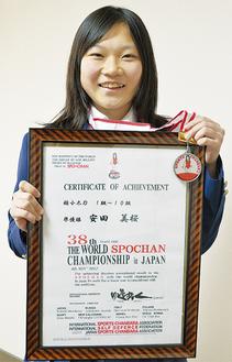 銀メダルと賞状を掲げる安田さん