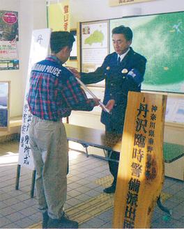 閉所式で齋藤署長(右)にピッケルが返還された