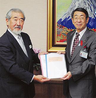 報告書を古谷市長に手渡す本間委員長(左)