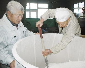 米を混ぜる作業。内山さん(左)の経験が生きる