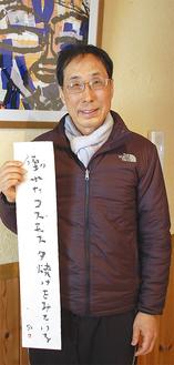 橋本樸樸さんの絵の前で直筆の大賞作品を持つ井上さん