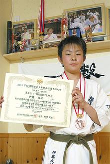 今大会のメダルを掛け賞状を持つ伊藤さん