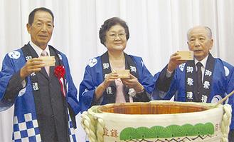 祝賀会で鏡開きの後、乾杯をする飯田理事長(中央)
