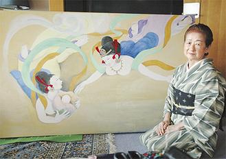 壁画作品の1つ「赤ちゃんを地上に運ぶ天女」の前に座る作者の紫藤さん