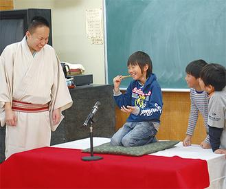一左さん(左)の前で、そばを食べる身振りに挑戦する児童