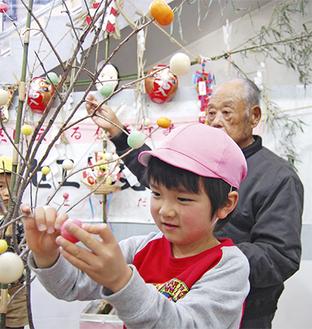 前場さんと一緒にコナラの枝に団子を飾る園児