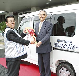秦野ライオンズクラブの高橋実行委員長から模造キーを受け取る藤村会長(右)