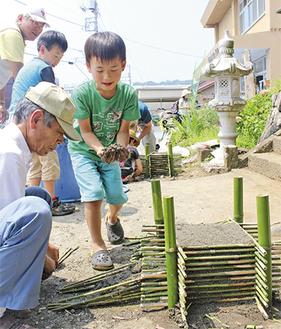 教わりながら土を運ぶ児童